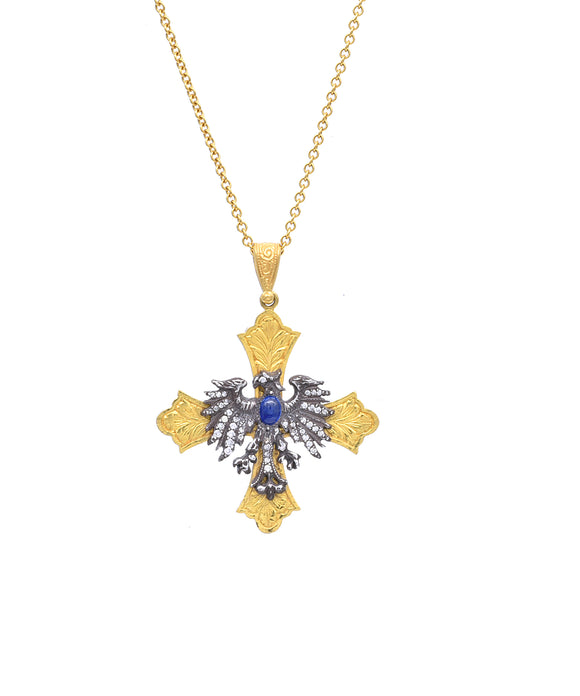 "An heraldic eagle spreads its wings for this interesting pendant. The sterling silver eagle is set with diamonds and a sapphire. It's mounted on a 22k gold engraved cross. The cross is 1 1/2"" across and hangs from a 22"" gold link chain."