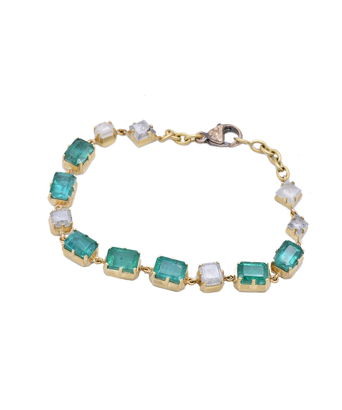 "Here's a modern way to enjoy emeralds. Over 12 carats of emeralds are set along the bracelet with rough diamonds totaling 5.05 carat. The 18k yellow gold bracelet is 7.25"" long."