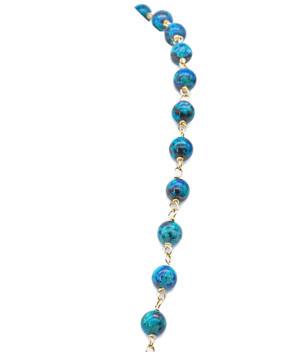 "Traditionally favored as a stone of prosperity and business astuteness, chrysocolla displays lovely shades of blue and green. We've wire-wrapped 8mm beads with 14k yellow gold for a fresh look. The necklace is 30"" long."