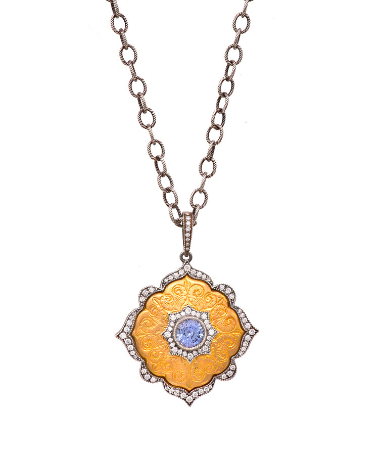 "The intricately engraved locket stars a fabulous bright blue sapphire center. Diamonds totaling .55 carat define the edges. The 22k gold and sterling silver locket has a hinged crystal back to reveal and protect your treasure. The locket is 1 3/8"" in diameter and hangs from a textured link 26"" chain."