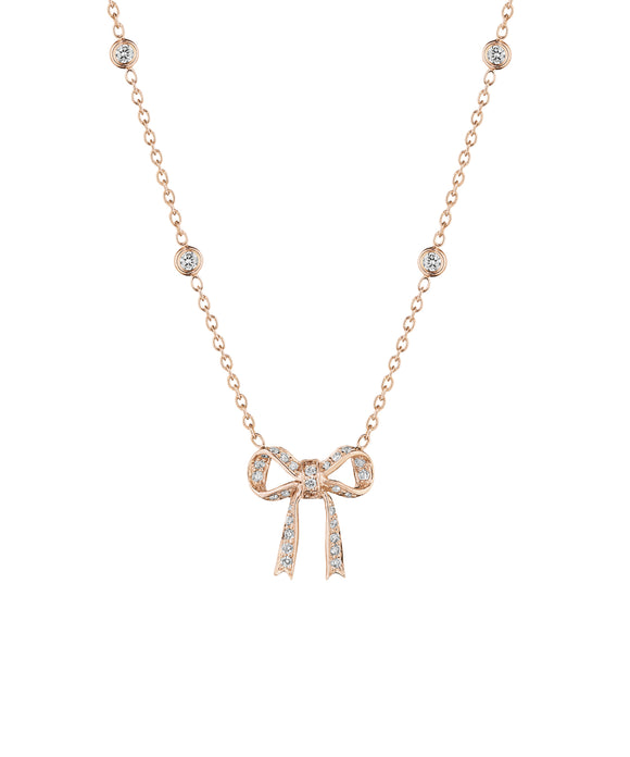 "The sweet little 18k rose gold bow hangs from an 18"" adjustable chain set with diamonds. Total diamond weight is .58 carat. The bow is about 5/8"" across,"