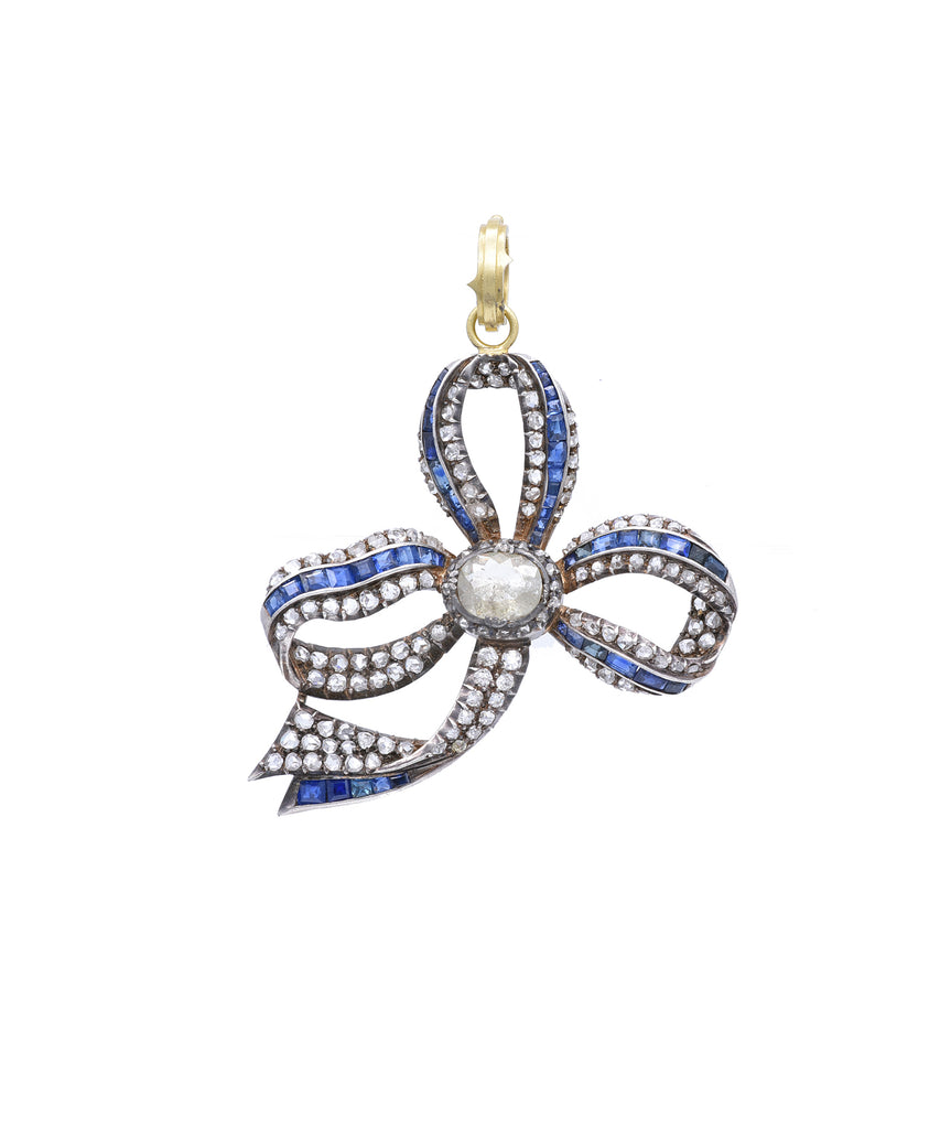 Sylva has set a sparkling rough diamond in the center of this vintage diamond and sapphire bow pendant. It blends beautifully with the old cut diamonds. The 18k yellow gold bow is 2 ' across and hangs from an 18k yellow gold hinged bale.
