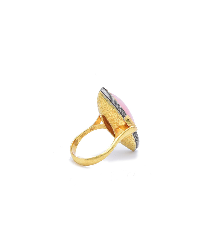 "This dramatic ring is great on an index finger. The marquis pink opal weighs 9.95 carats. It is flanked by marquis rubies totaling 1.24 carats. Add .28 carat of diamonds for sparkle. The 22k gold and sterling silver ring is 1 3/8"" tall in front."