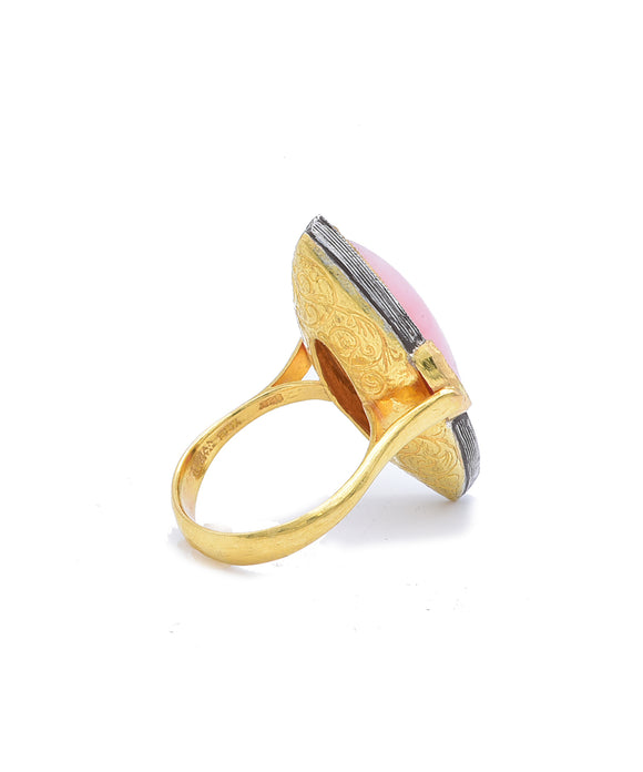 "The graceful navette shape of the pink opal is flattering to any finger. The opal is outlined with diamonds totaling .31 carat. The beautiful engraving continues to the back of the ring. The 22k gold and sterling silver ring is 1 3/8"" long and size 6 1/4."