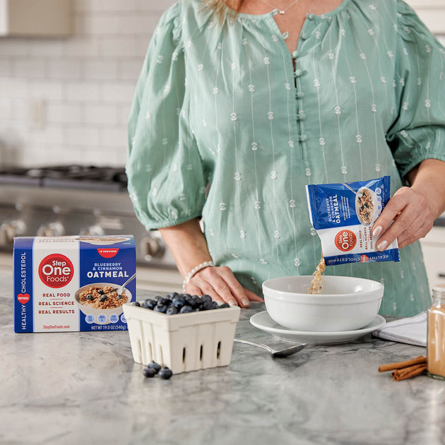 A woman in a mint green shirt pouring the Bluerberry Oatmeal package into a white bowl with a carton of blueberries and cinnamon sitting on a marble countertop