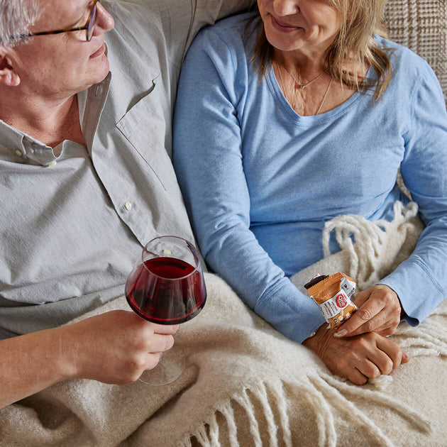 A man and a woman sit on a plaid couch looking at each other enjoying a glass of red wine and a Peanut Butter Bar