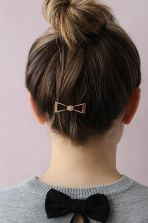 Plated brass bow barrette in rose gold plating finish worn as hair pin in back of head below hair bun