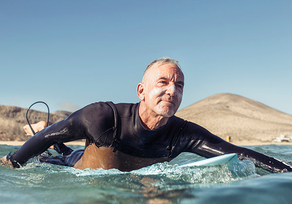 Man Surfing with Sunscreen on his face.