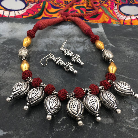 Oxidised leaf amulet necklace in red thread and golden dholki beads