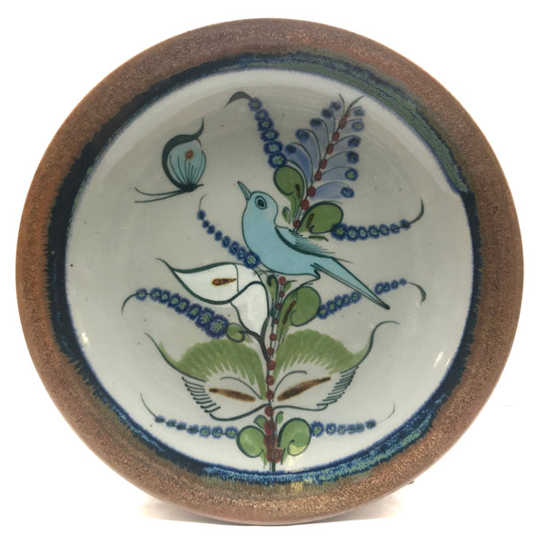 This buffet plate has natural grey clay color background with a brown rim and blue and green bird, butterfly and flower.