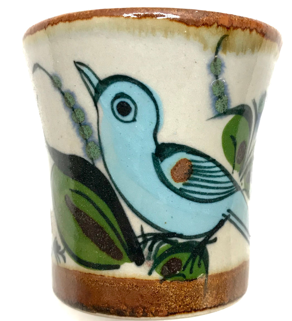 Brown rim and bottom with natural grey clay color and bird, butterfly, plant life on exterior