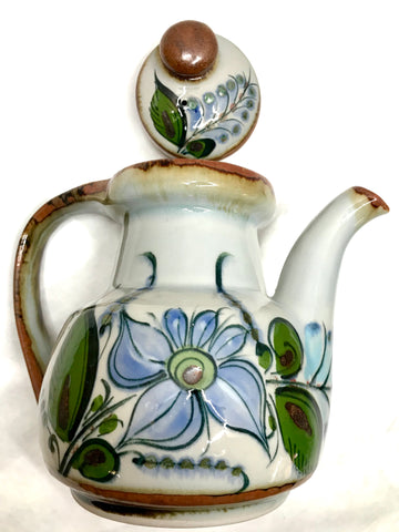 A teapot with a lid with brown trim and grey background with green leaves and blue flowers.