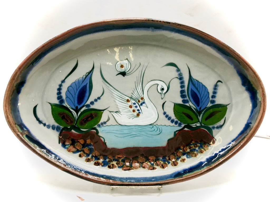 An oval platter with brown trim and bird, butterfly and plants.