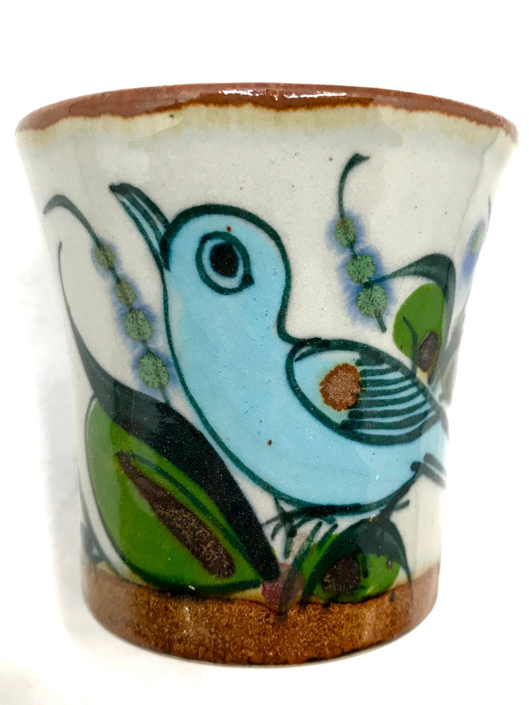A mini drinking cup with brown rim and bird on exterior.