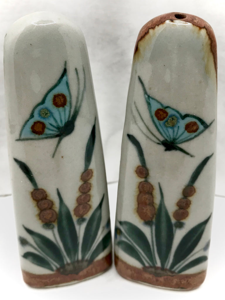 One brown tip, one natural grey clay color tip, both with blue butterflies and green and brown plant life.