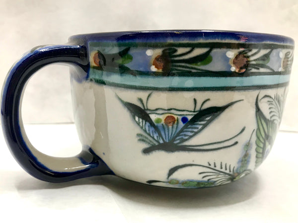 Blue rim cup with blue handle used for latte and has butterfly and plants on exterior.