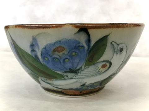 A brown rim bowl with a decorated exterior in birds and plant life.