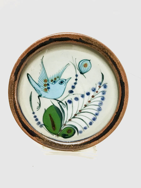 Round tray with brown rim, natural grey color background with bird, butterfly, and plant.
