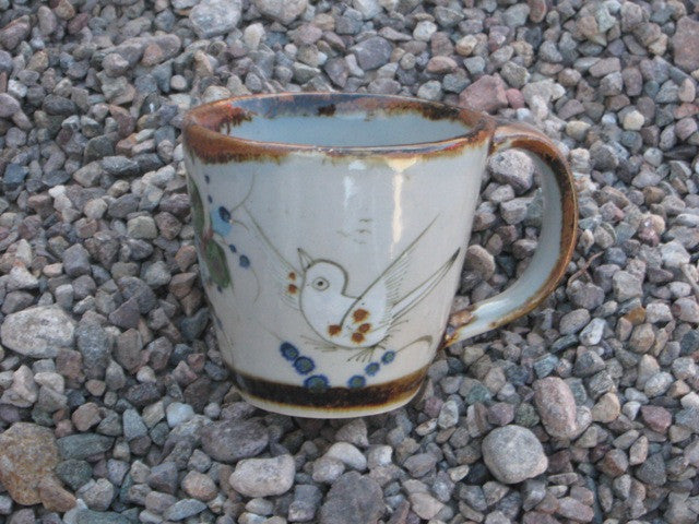 Ken Edwards Large Conical Mug with natural grey clay background, brown rim and handle with bird or butterfly or plant life or all three.