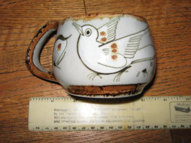 Ken Edwards Mug T 8 is a rounded squatty mug with brown rim and bird and butterfly decoration exterior.