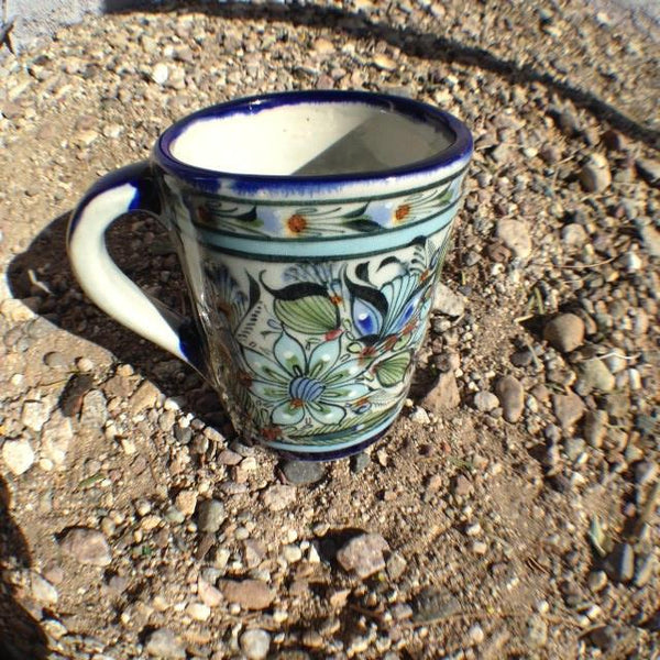 Blue rim mug with blue handle and bird, butterfly, and plant life decoration exterior.