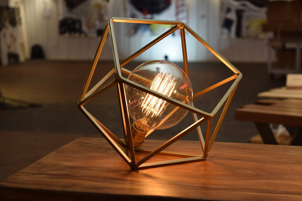 This geometric table lamp comes with your choice of bulb. Here is the cage Edison bulb, which gives off a warm, softer glow | Mercedes Table Lamp - Gold | Wayne Works