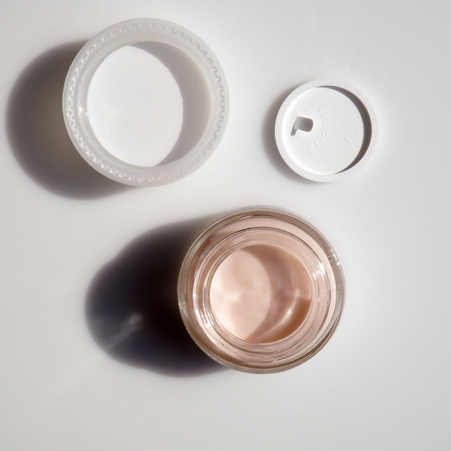 An image of Crème de la Crème Firming Anti-Aging Cream face up with the cap laying next to it.
