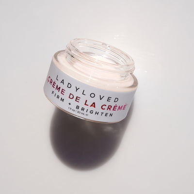 An image of Crème de la Crème Firming Anti-Aging Cream laying face up with its cap removed.