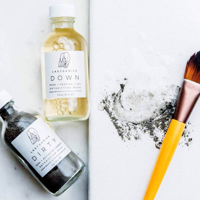 Image of Down & Dirty Detoxifying Mask with both bottles laying face up, and a paintbrush with mixed ingredients next to them.