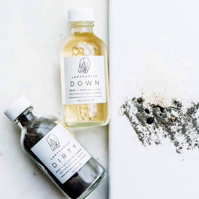 Image of Down & Dirty Detoxifying Mask with both bottles laying face up, and the ingredients lightly mixed on a raised platform next to them.