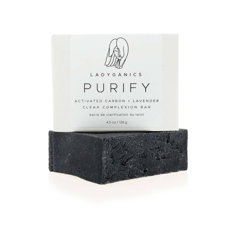 An image of three Purify Clarifying Charcoal Soap bars sitting on top of each other, with the group sitting on a piece of stone architecture.
