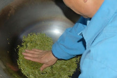 Tea Master hand roasting long jing leaves