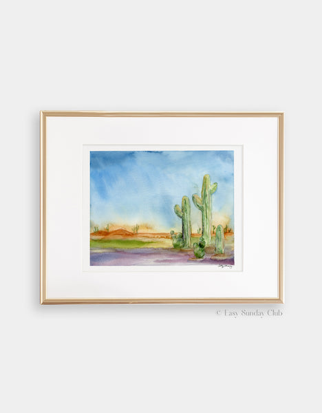 gold-framed mock up cactus watercolor in a desert landscape, desert themed art print with bright and saturated colors