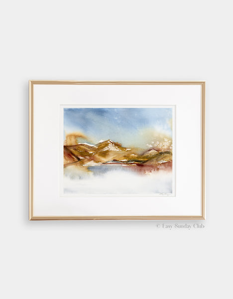 Gold framed mock up of rich earth-tone washes of color reveal a desert hill watercolor landscape