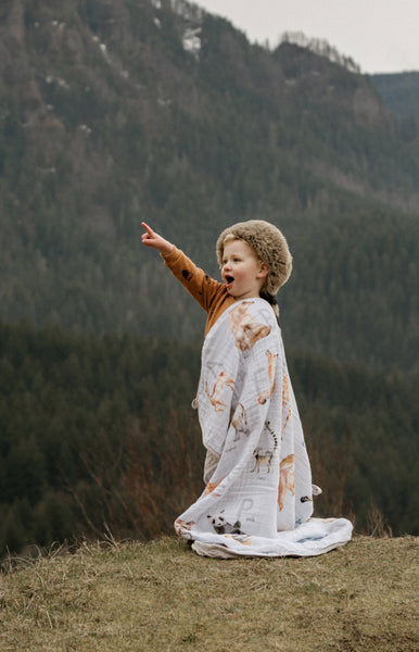 toddler wearing his raccoon hat and Alphabet Blanket as a cape in the mountains. He's pointing at a bird flying by and expressing his excitement.