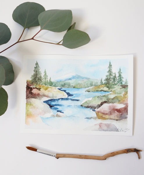 rocky stream rolls down from a mountain tucked away in a forest watercolor landscape flat lay