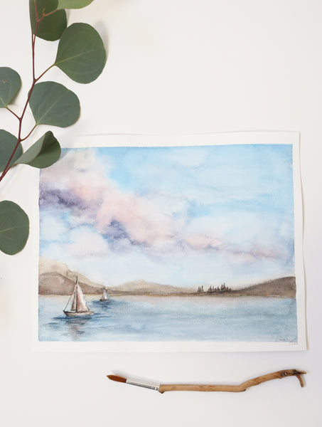 cotton candy skies with puffy clouds above a sailboat dotted lake watercolor landscape flat lay