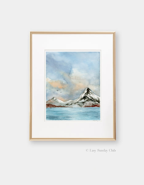 Gold framed mock up of cold, bright lake with snowy mountain and cumulus clouds in watercolor
