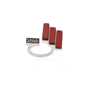 "Red Skyline Ring - Inspired by the city skyline, this handcrafted ring is made of 925 sterling silver. This piece features 3 custom-made rectangular resin stones and Arabic calligraphy that reads "" حبك موطني"" which translates to ""your love is my home"".  Stone color: Brick red  Size: Adjustable  Weight: 7.42g"