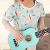 Little kid wearing mint summer tee with tropical motives and ukulele