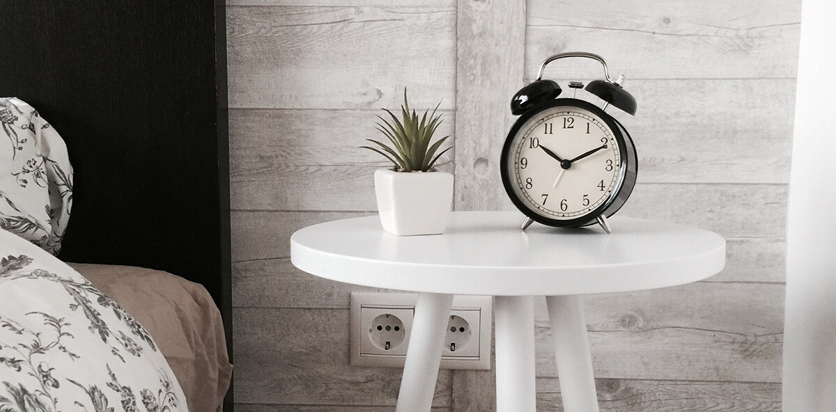 Alarm clock next to a bed before breakfast to symbolize how caffeine keeps you awake