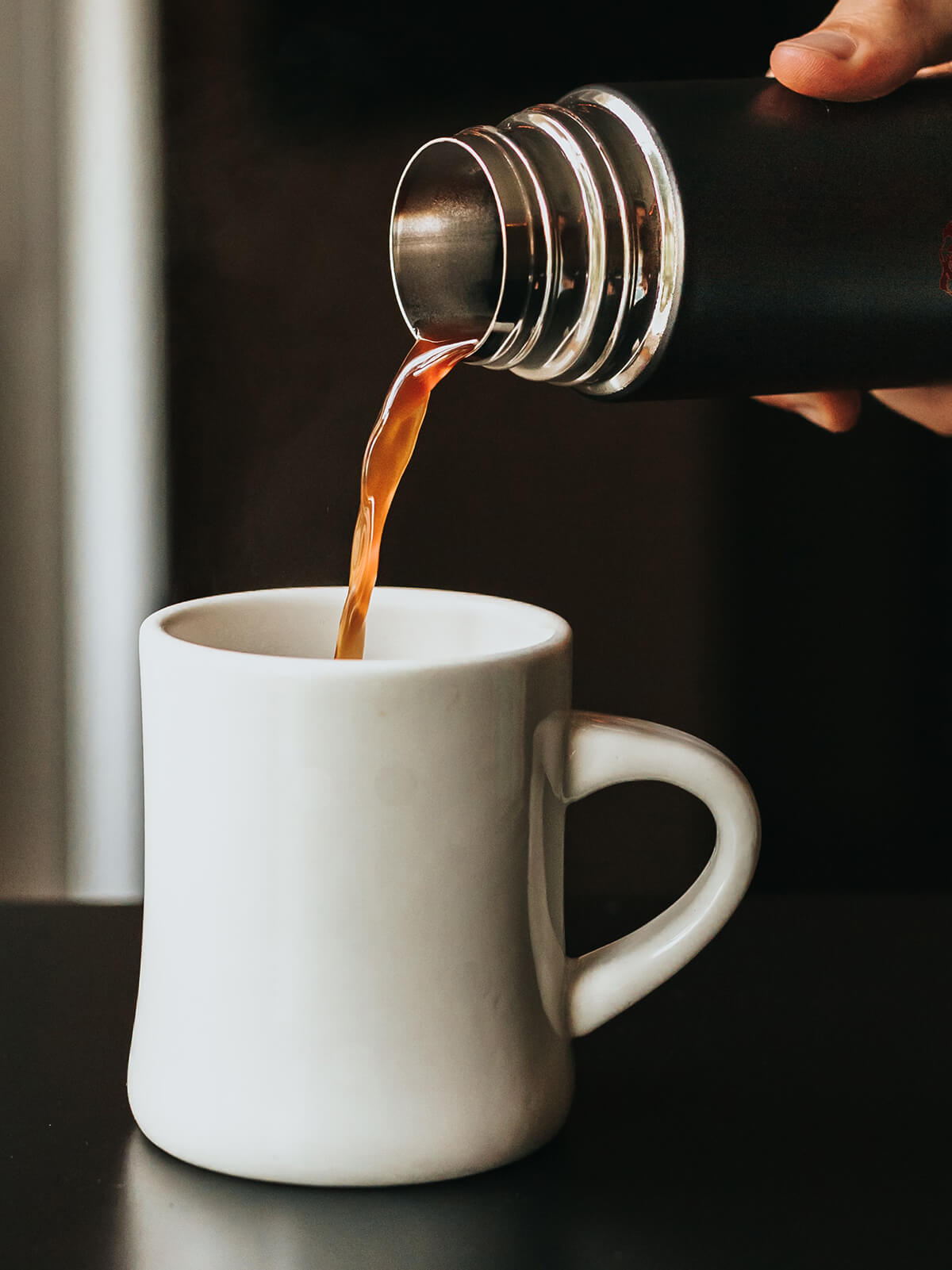 Black coffee being poured out of a thermos