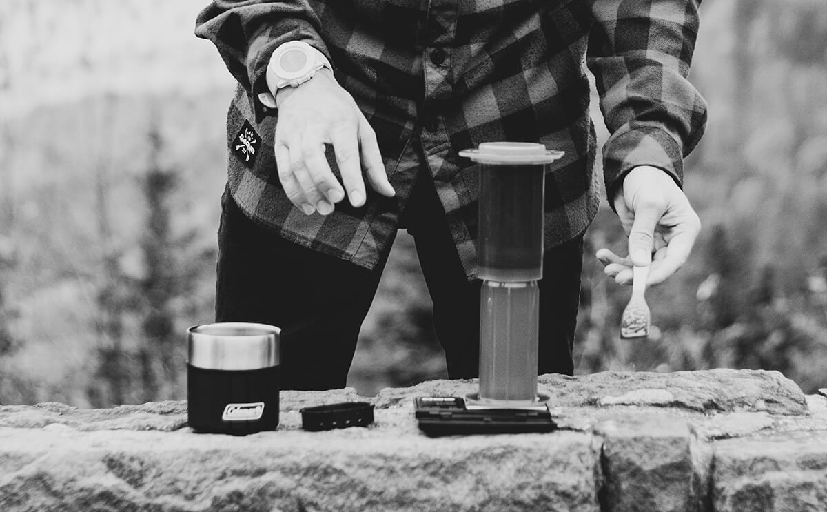 Man brewing inverted AeroPress coffee outdoors
