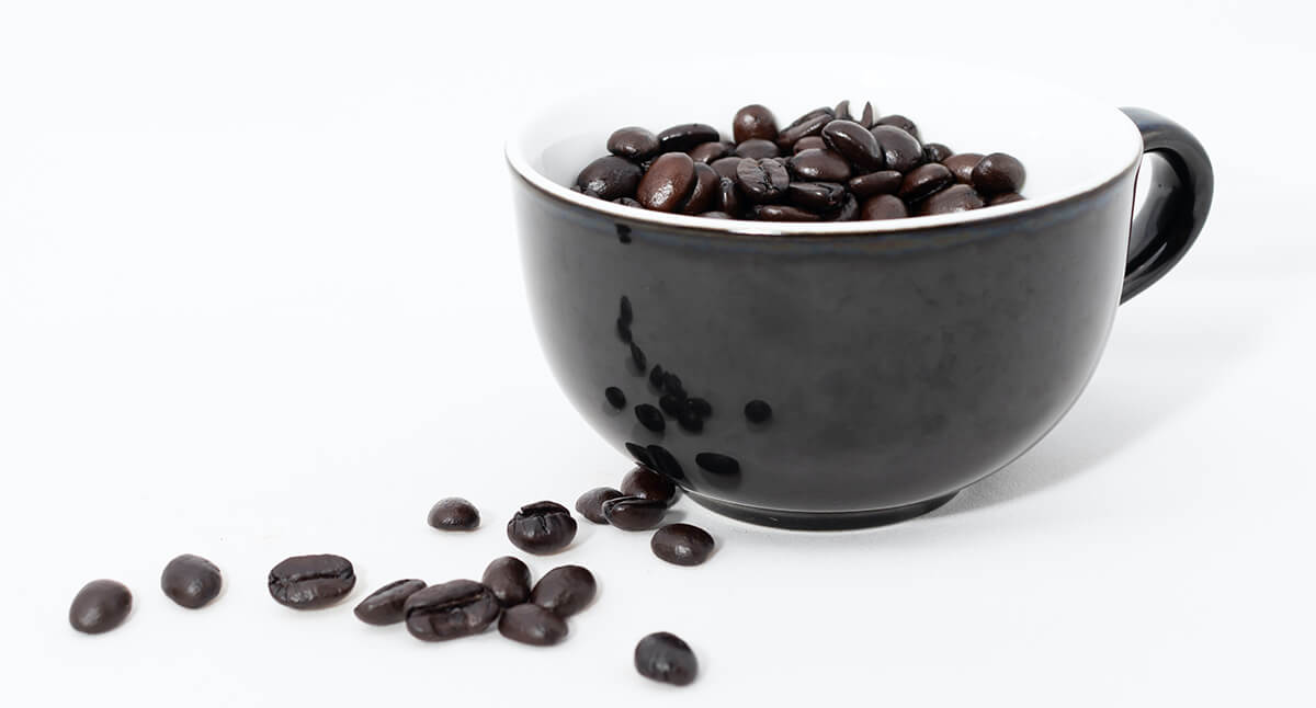 Some dark roast coffee beans in a cup