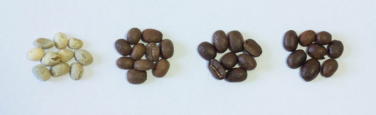 Some light roast coffee beans next to other types of roasts