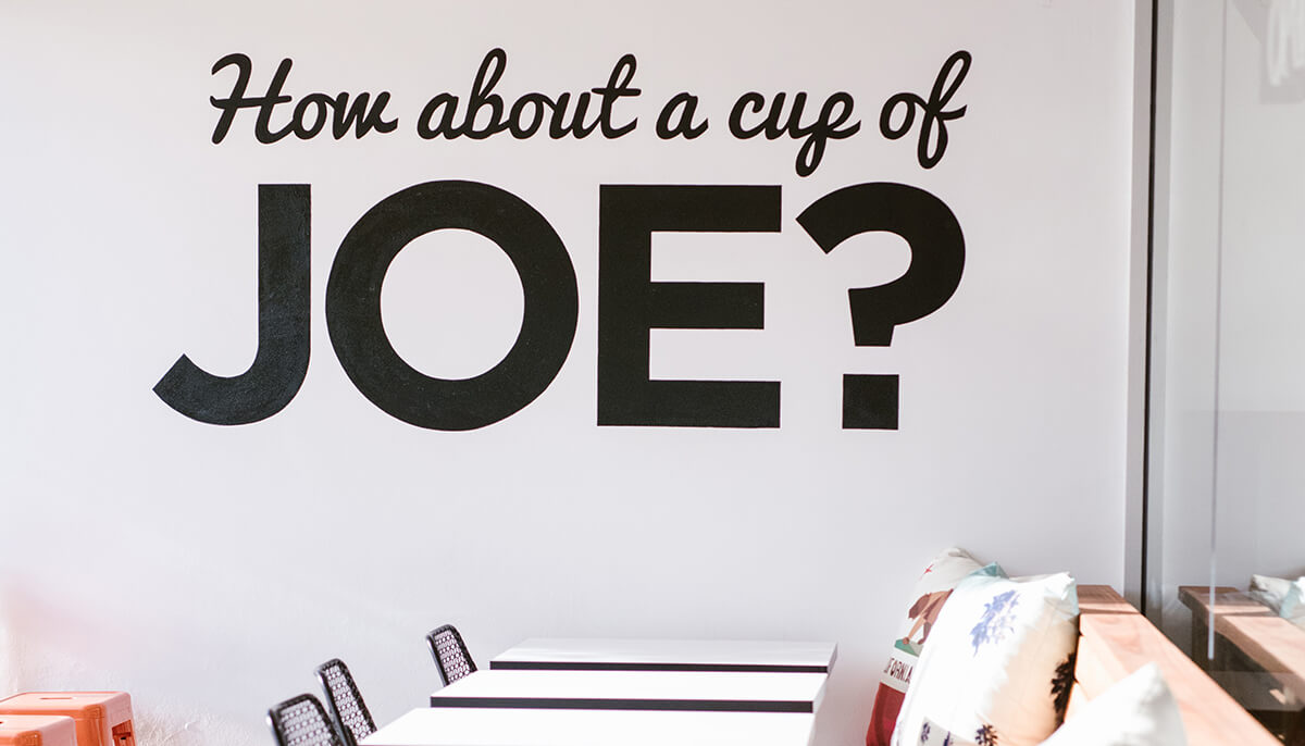 Wall showing a writing saying 'How about a cup of joe'