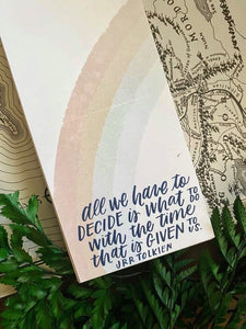 "LOTR notepad featuring a watercolor rainbow and the quote ""all we have to decide is what to di with the time that  Is given to us."""