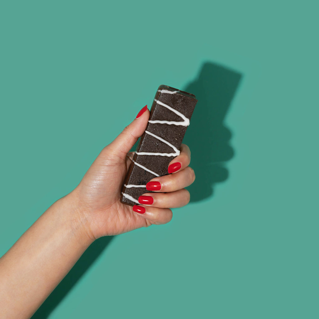 Woman's hand holding fitjoy protein fiber bar
