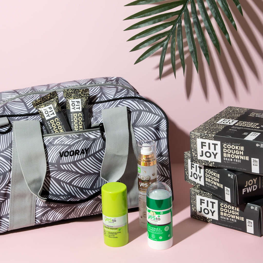 gym bag next to fitjoy protein bars, deodorant, body spray, and a palm frond