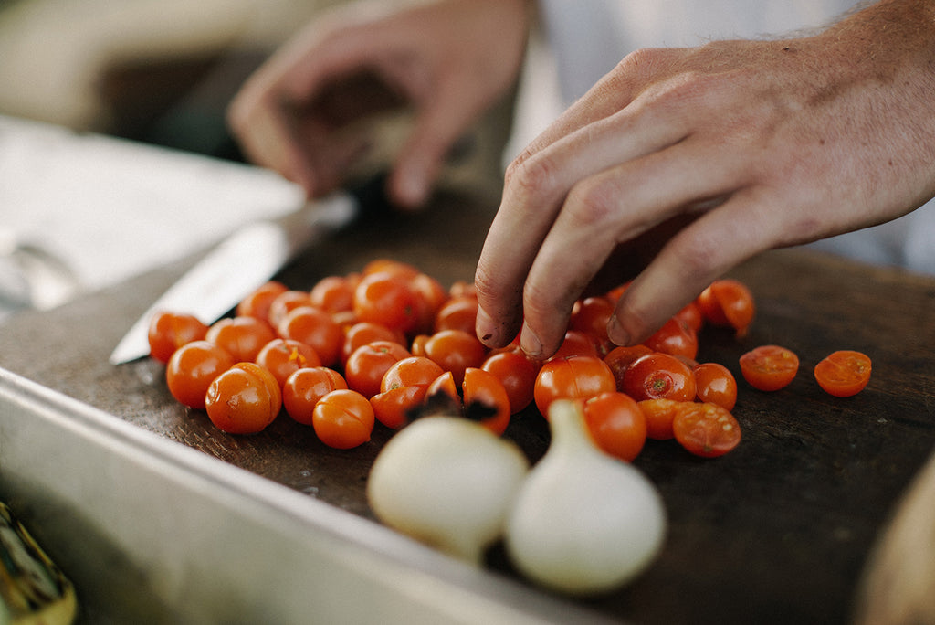 hands chopping tomatoes and garlic